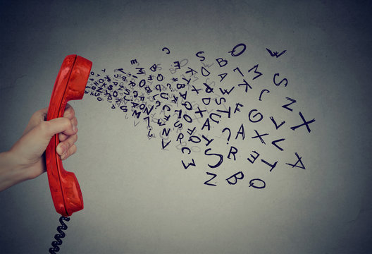 Hand holding telephone handset with alphabet letters coming out. Too many words
