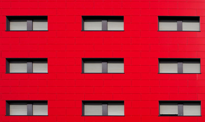 Bright red facade of a modern residential building with gray shutters