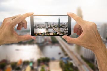 Man's hands holding smartphone taking photo of Bangkok city,Thailand