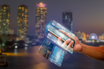 Man's hand holding smartphone with transparent multi screen on blurred city night light, communication technology concept Wall mural