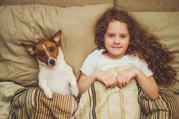 Cute child and puppy under quilt.
