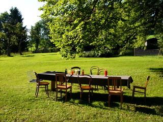 Lange Tafel mit Tischdecke und Holzstühlen auf grüner Wiese bei einem Bauernhof in Rottenbuch im schönen Oberbayern