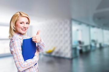junge lachende Geschäftsfrau vor Büro-Hintergrund