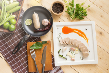 Steamed pork sausage in a white plate served with Thai traditional style chili sauce