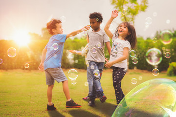Kid and friends in international pre school play a bubble in playground