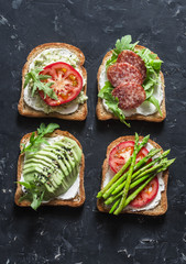 Toast sandwiches with avocado, salami, asparagus, tomatoes and soft cheese on dark background, top view. Tasty breakfast, snack or appetizer to wine