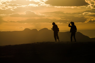 Silhouettes of two people walking on White Sand Dunes during sunset in New Mexico