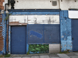 abandoned derelict shop with storefront boarded up with peeling blue paint decaying facade and exposed tiles and brickwork