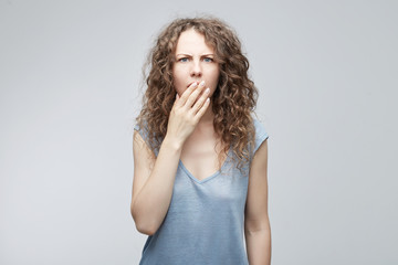 Portrait of amazed surprised young beautiful curly-haired  female wearing grey t-shirt having astonished face expression, covering open mouth with hand,looking at camera in shock,full disbelief