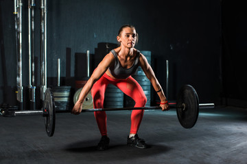 Muscular young fitness woman doing heavy deadlift exercise in crossfit gym
