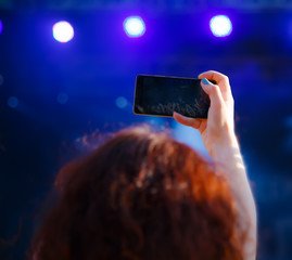 Woman with phone shooting concert, view from behind, blur effect