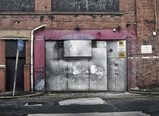 derelict abandoned commercial property awaiting demolition or redevelopment with boarded up entrance and decaying brickwork in an empty road
