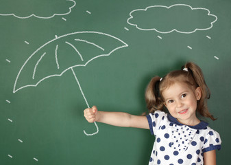 child girl hold umbrella near school blackboard, weather concept