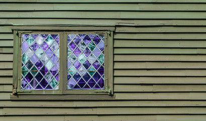 2 windows with purple panes in a leaded diamond pattern on the wall of a colonial building with copy space