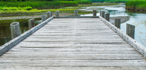 weathered gray wooden dock overlooking a shallow river and marshland