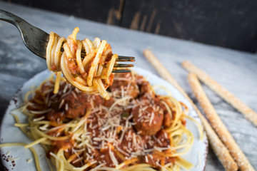 Plate of spaghetti and meatballs with fork and breadsticks