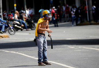 A demonstrator gestures while clashing with riot security forces during a rally against Venezuela's President Nicolas Maduro's government in Caracas