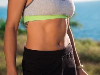 Young Active Sporty Successful Woman Standing on the high hill above sea or ocean and shows her press on stomach. Beautiful girl in sportswear. Health concept.