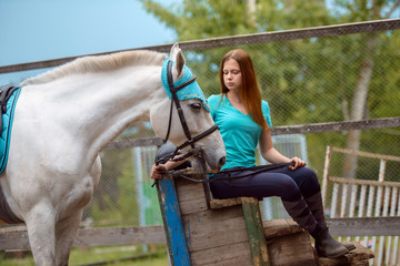 Girl rider and her horse to rest near the stable after riding