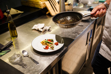 Food concept. Preparing traditional italian food. chef in white uniform decorate ready dish in interior of modern restaurant kitchen.