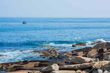 rocky coast of the Atlantic ocean with fishing boat in the distance at Cape Ann, Massachusetts