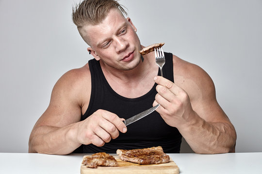 Close up big body bodybuilder eat big beef steak behind table opposite gray wall
