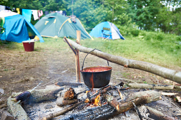 Bowler with soup on campfire and tourist tents