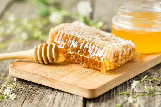 Honeycomb on wooden board with honey spoon