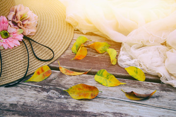 delicate scarf, hat and golden dry leaves on old wooden table outdoor in the park