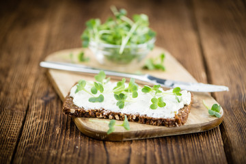Wooden table with healthy food (slice of bread, cream cheese and fresh cutted cress)