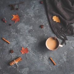 Autumn composition. Cup of coffee, blanket, autumn leaves on black background. Flat lay, top view, square