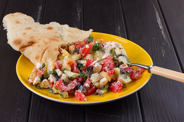 Salad of tomato pepper feta in a yellow plate