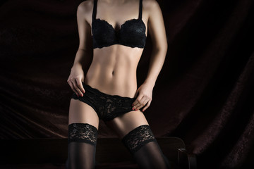 Woman body in black lingerie and stockings on the black background. No face
