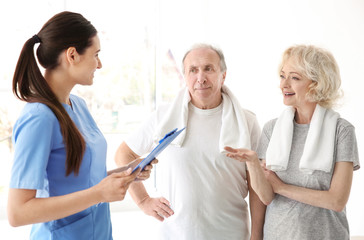 Physiotherapist with elderly patients in modern clinic