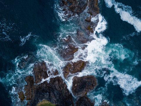 Aerial shot of waves hitting rocks on ocean coast