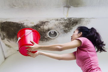 Young woman collecting drops rainwater