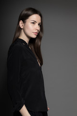 European attractive sexy fashion model with natural brunette hair, posing in studio, wearing black shirt, dark background, beauty photo shot, retouched image