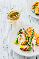 Salad with fried halloumi, asparagus and orange zest. White wooden background