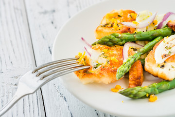 Salad with fried halloumi, asparagus and orange zest. Close up. White wooden background