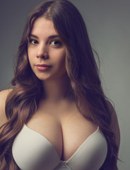Young girl with big breasts posing in a bra