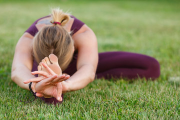 Details of the hands of a young woman practicing yoga on a urban wall
