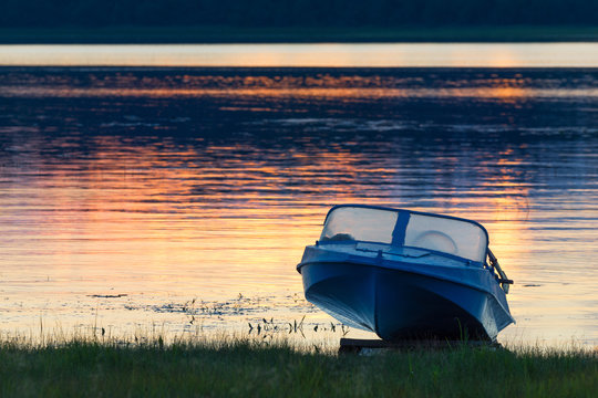 """Kenozersky National Park, Russia. An old blue aluminum motorboat called """"Kazanka"""" on the lake shore at sunset. Blue boat on the shore, close-up.A typical lake landscape of the North of Russia."""