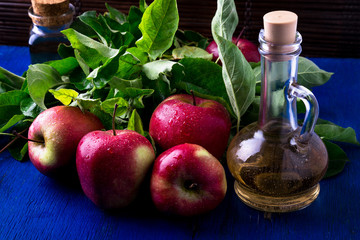 Apple cider vinegar. Three glass bottle on blue background. Red apples