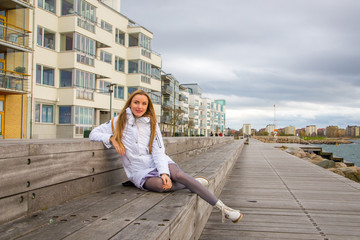 Girl sitting at the cute district of the Western Harbour in Malmo (Vastra Hamnen)