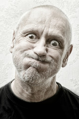 Black and white portrait of a funny and crazy caucasian man making faces with eyes round like balls and puffy cheeks