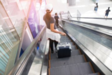 BANGKOK, THAILAND - AUGUST 8, 2017: Blurred background of asian woman with luggage suitcase on escalators at Suvarnabhumi Airport. The most popular SE Asia aviation hub.