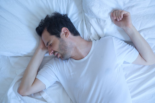 Thoughtful man cannot sleep because of insomnia