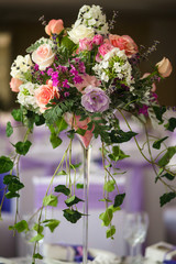 Vase and floral composition on the wedding served table in a restaurant