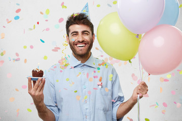People, joy, fun and happiness concept. Relaxed happy birthday guy looking cheerful, smiling happily, posing for picture, holding colorful helium balloons and cupcake with confetti falling down