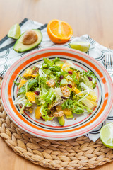 Fresh salad with orange, greens and avocado. Healthy diet food concept. View from above